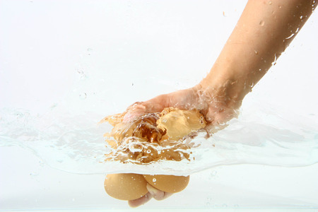 Eggs in hand into clear water splash Stock Photo