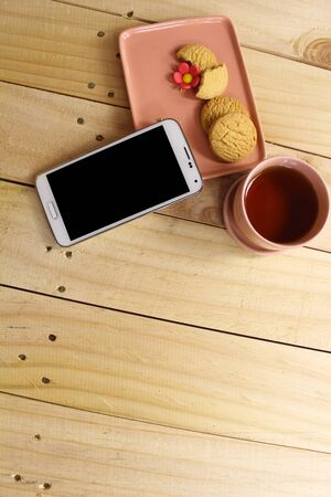 sugarcraft: mobile phone together with cookies and tea Stock Photo
