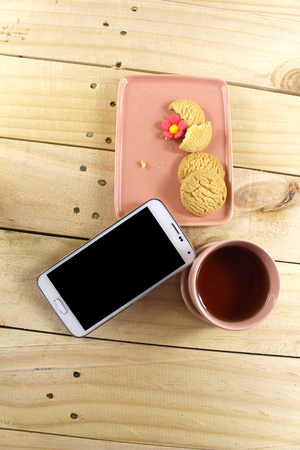 missing bite: mobile phone together with cookies and tea Stock Photo