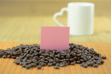 valentine day cup of coffee: white mug with heart handle with raw coffee with wood background and pink empty note Stock Photo