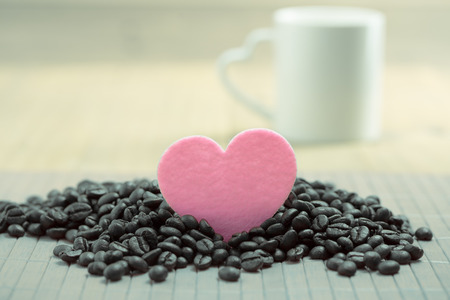 valentine day cup of coffee: white mug with heart handle with raw coffee with wood background  and pink heart