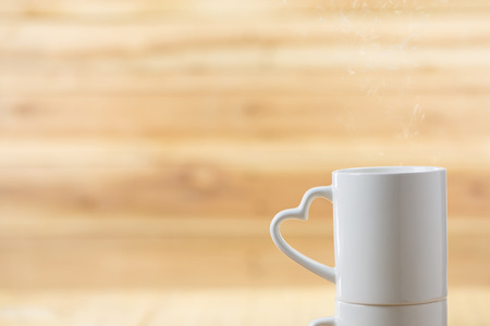 valentine day cup of coffee: White mug with heart handle with wood background