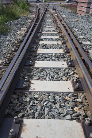 railroad tie: pile of concrete railroad tie with train as background