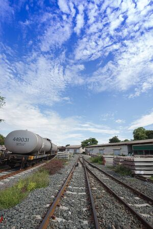 pile of concrete railroad tie with train as background