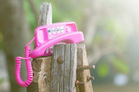 waiting phone call: Pink telephone on old talble in nature