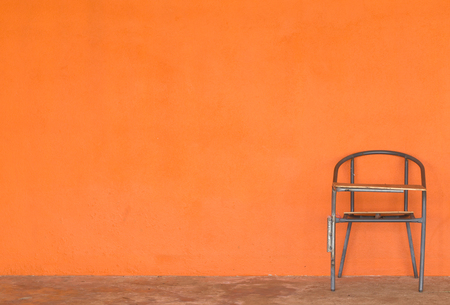poor wood and steel chair on cement floor and orange wall with copy space for text on all of left hand of photo Stock Photo