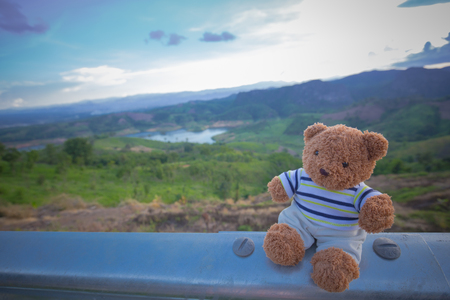 cloud scape: Teddy bear doll sit on steel bar with landscape and cloud scape Stock Photo