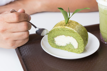 Man eating creamy green tea roll with fresh green leaves on white plate Stock Photo