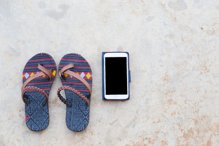 Traditional cloth slipper and mobile phoen in red case on concrete floor
