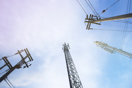Telecommunicatiion wire and steel pole and electricity wire and concrete pole in blue sky with purple tone present UV ray Stock Photo