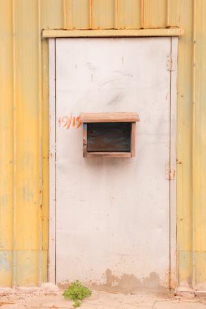 Grunge steel door with shutter old yellow wall