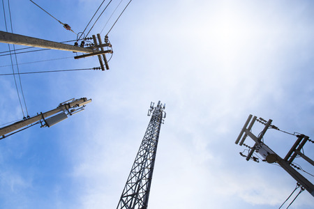 Telecommunication wire and steel pole and electricity wire and concrete pole in blue sky with aura light near the corner Stock Photo