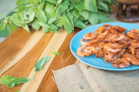 Deep fried crispy shrimp on blue ceramic plate on wood table