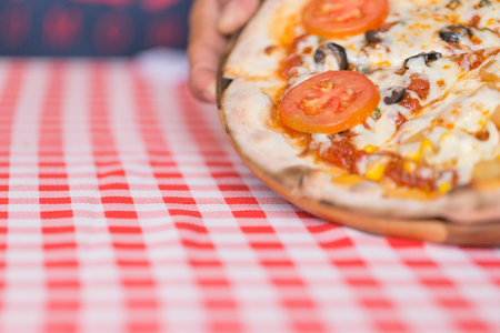 Thin Pizza on wood plate on red and white table runner