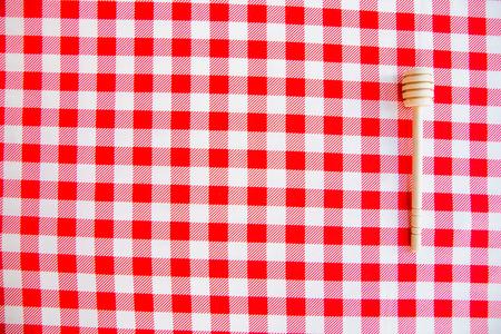 Honey spoon, kitchen utensil on red and white checker table runner