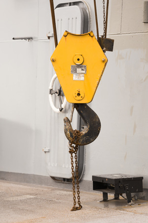 Big yellow crane with rustic chain with ships door background
