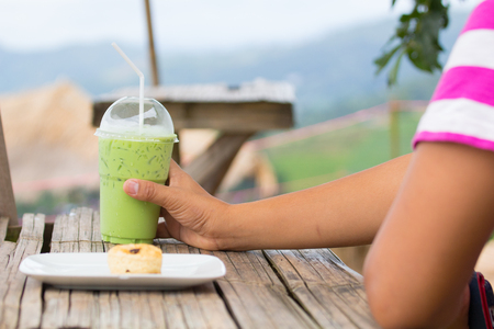 Green tea latte in plastic cup and lid with white straw as famous japanese millk shake beverage on man hand Stock Photo