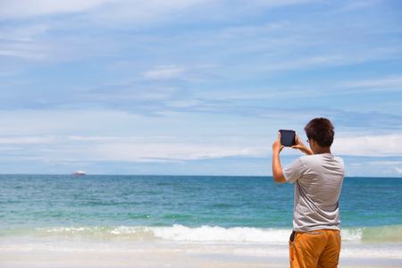 Asian man with eyeglasses with grey T-shirt and orange pants holding tablet shooting seascape  with calm blue  sea and  blu sky
