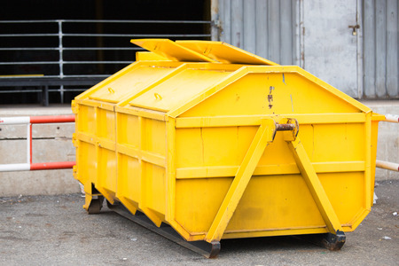 Yellow big old steel trash with garbage
