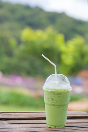 Iced milk green tea in plastic cup with lid and white straw on bamboo table in nature