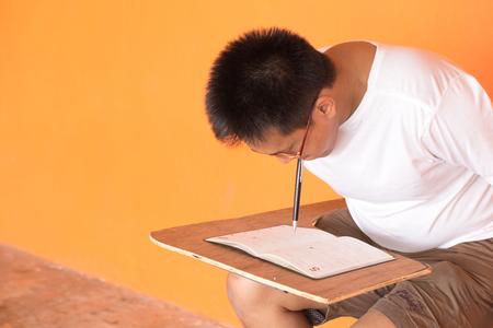Handicap sitting Asian man having book on orange wall