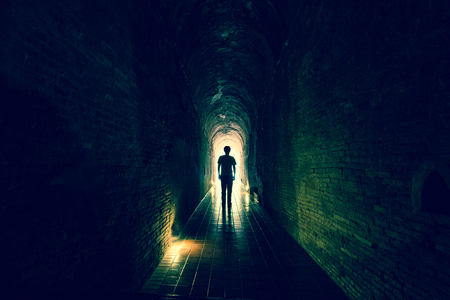 Man silhouette forward to  exit of stone cave with light as concept