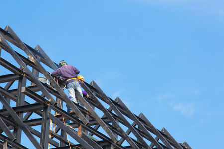 Worker working on steel and iron roof of underconstructed building