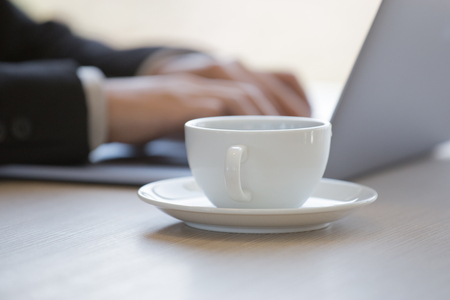 White coffee cup and businessman typing laptop as blurred bacground Stock Photo