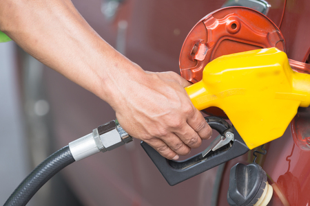 Filling petrol line into fuel inlet Stock Photo
