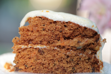 A piece of carrot cake with creamy white chocolate on white ceramic plate with steel spoon