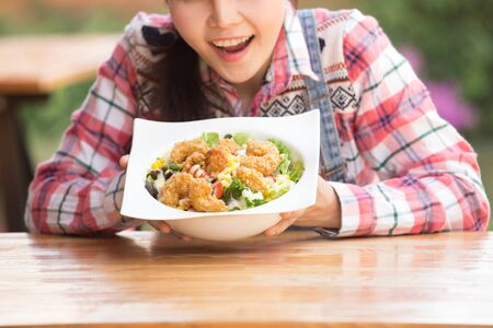 Asian woman enjoying her healthy salad with crispy salad in big white bowl on the table outdoor in garden