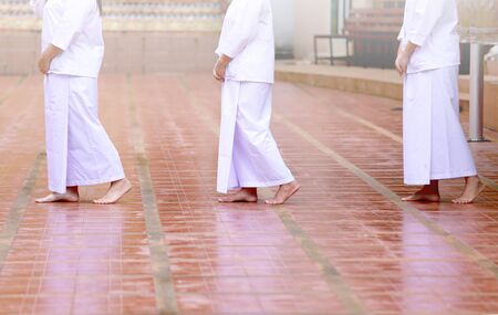 Buddhism in white cloth practicing meditation by tranquil walk. Female in white cloth buddhism walking in temple for meditation. Jong Krom