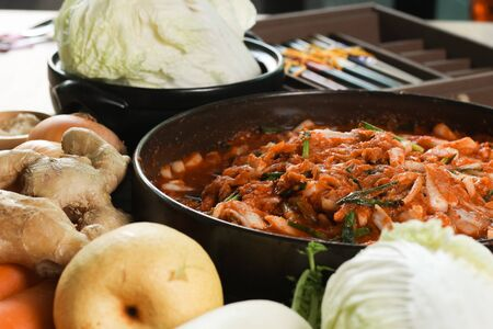 Kimchi preparation. Korean cuisine famous side dish, fermented vegetables, cabbage, radish, spicy and smelly seasonings including apple or pear, onions, garlic, ginger & spring onion