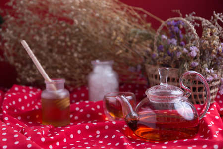 Tea pot and tea cup on wood table with honey and suagr in mag with flower basket on red cloth napkin