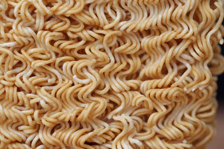 Crispy and dry instant square noodle. Uncook and unhealthy dried noodle on wood pallet.