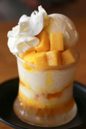 Sweet yellow mango bingsu, modern korean cold dessert or korean ice cream in glass. Tasty and famous summer sweet.