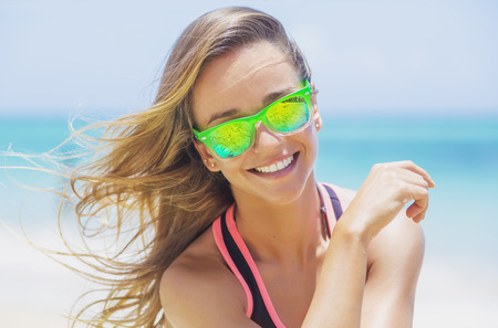 Young, cute, tanned girl who loves the beach, kite surfing, sports. A lovely smile, wide-eyed, lively blonde hair