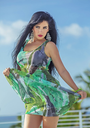 Sexy latina with long black hair and green fashion dress Stock Photo