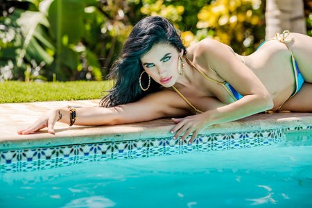 Sexy latina with long black hair at the pool