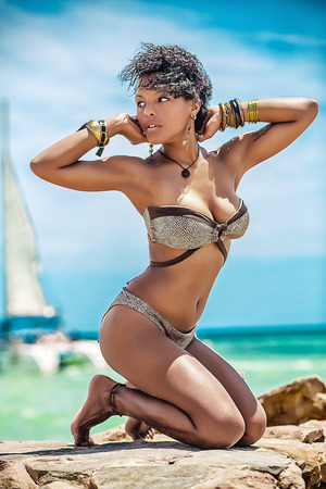 Beautiful curly mulatto in bracelets and bikinis at the sea