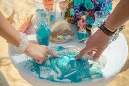 Hände des Brautpaares bei der karibischen Sandzeremonie