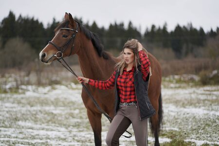 A beautiful girl in a fashionable shirt walks with her horse in early winter.