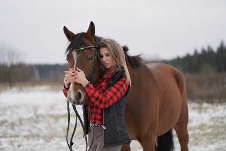 A beautiful girl in a fashionable shirt lovingly embraces horse. Early winter. Christmas. Space for text on white background