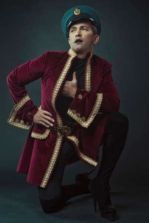 a man portraying a glamorous character in a maroon suede tailcoat and cap, on a black background