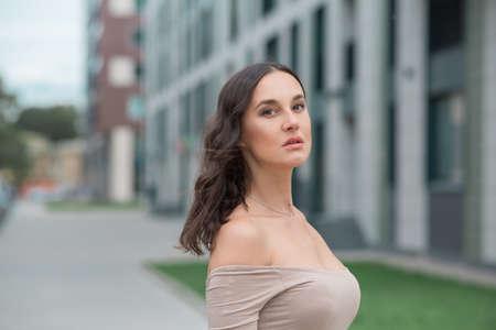 portrait of a beautiful woman in a beige dress with a neckline Фото со стока