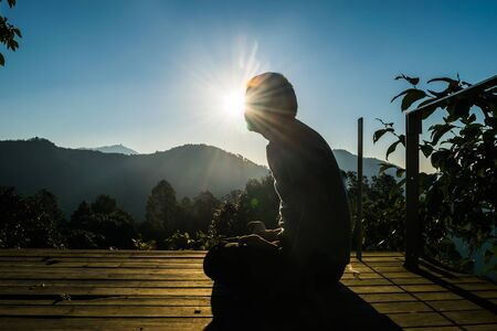 Meditation with yoga exercises in the beautiful mountain valley of Uttarakhand in India