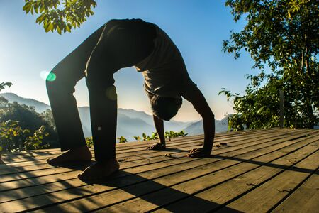 Meditation with yoga exercises in the beautiful mountain valley of Uttarakhand in India, the name of the pose is Sanskrit name Chakrasana or Wheel Pose