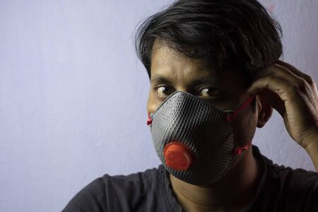 an Indian man wearing safety nose mask looking at camera white background corona virus or covid-19 protection