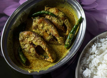 high angle view of hilsa fish curry with mustard paste and green chilli served on plate with rice