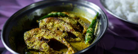 hilsa fish curry with mustard paste and green chilli served on plate along side rice with selective focus